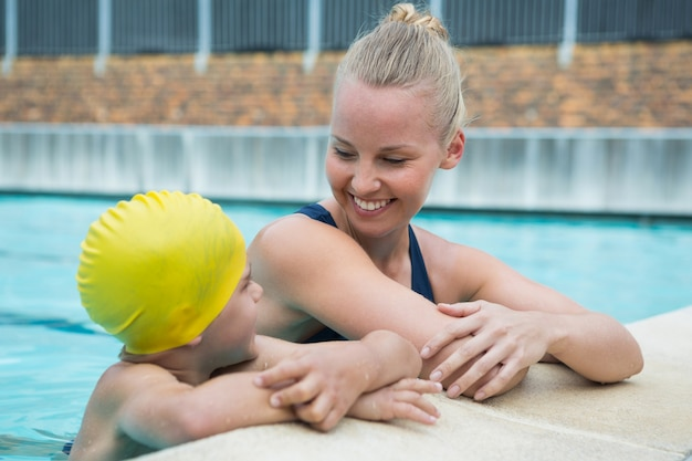 Instrutora feminina e menino relaxando à beira da piscina
