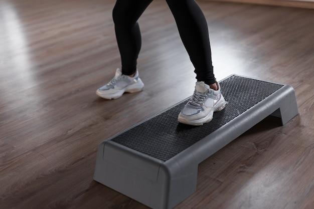 Instrutora profissional feminina com tênis esportivos elegantes e leggings, envolvida na preparação física na plataforma do ginásio