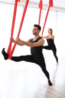 Instrutores de esporte fazendo atividades de ioga com roupas de cama