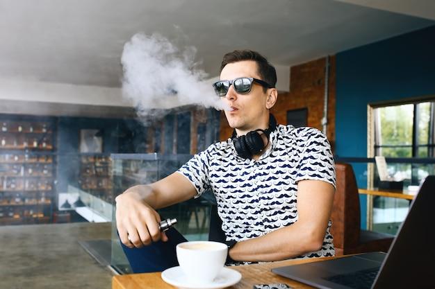 Insunglasse de homem jovem hippie bonito sentado no café com uma xícara de café, vaping e libera uma nuvem de vapor