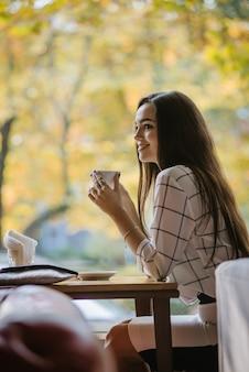 Integração dos muçulmanos na europa. jovem linda garota muçulmana adota a cultura europeia. uma jovem muçulmana está sentada em um café sem um hijab.