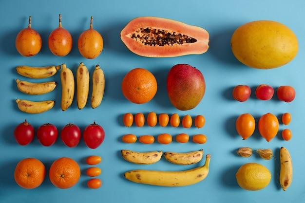 Inteiro e fatias de frutas exóticas isoladas no fundo azul do estúdio. cumquat, banana, fortunella vermelha, manga amarela, limão, pêssego, physalis. composição criativa de verão. nutrição essencial