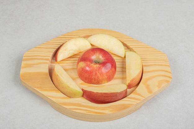 Inteiro e fatias de maçã vermelha na placa de madeira