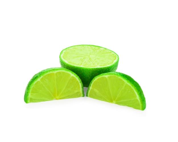 Inteiro e meio com uma fatia de limão verde fresco isolado na superfície branca