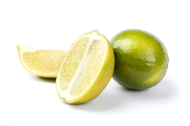 Inteiro e meio com uma fatia de limão verde fresco isolado no fundo branco