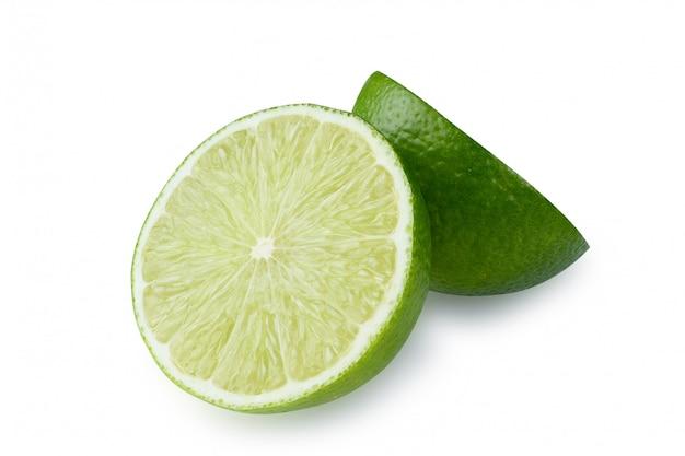 Inteiro e metade com uma fatia de limão verde fresco isolado com traçado de recorte