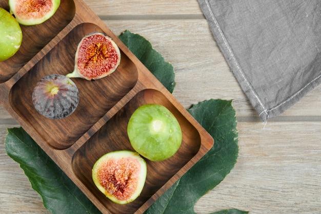 Inteiro e rodelas de figos verdes e pretos numa travessa de madeira com uma folha e uma toalha de mesa.
