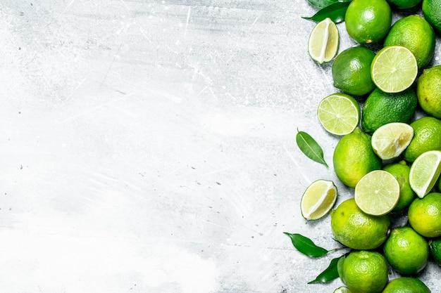 Inteiros e pedaços de limão fresco com folhas na mesa rústica
