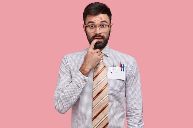 Intelectual indeciso mantém dedo perto da boca, tem barba espessa, veste camisa formal e gravata, usa óculos grandes