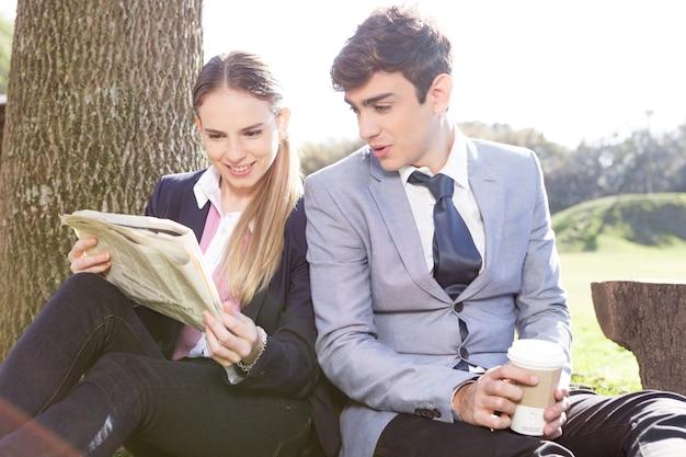 Inteligente casal lendo um jornal