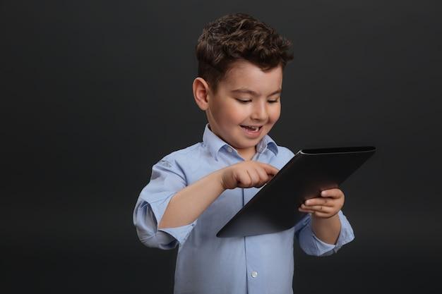 Inteligente desde a infância. adorável doce menino inteligente inclinando-se para a tecnologia moderna enquanto usa o gadget e fica isolado em um fundo cinza