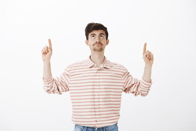 Intenso descontente atraente homem europeu com barba, olhando e apontando para cima com expressão de decepção, ficando impressionado com o trabalho de conserto na sala, em pé