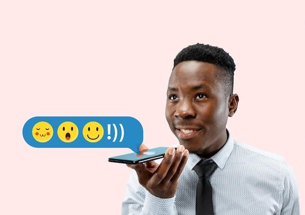 Interações de mídia social no celular. marketing digital na internet, conversando, comentando, curtindo. sorrisos e ícones acima da tela do smartphone, que segurando pelo jovem no fundo rosa do estúdio.