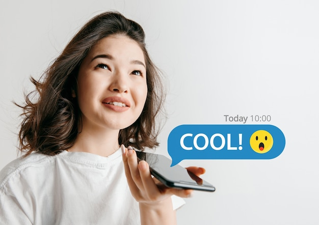 Interações de mídia social no celular. marketing digital na internet, conversando, comentando, curtindo. sorrisos e ícones acima da tela do smartphone, que segurando por uma jovem no fundo branco do estúdio.