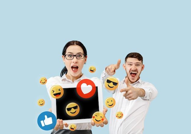 Interações de mídia social no celular. marketing digital na internet, conversando, comentando, curtindo. sorrisos e ícones acima da tela do tablet, que segurando pelo jovem casal no fundo azul do estúdio.