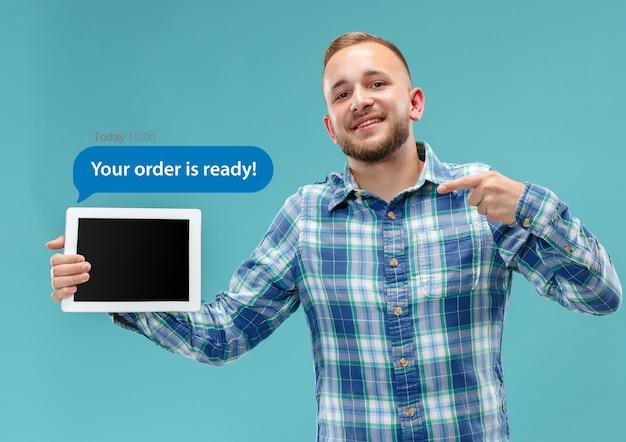 Interações de mídia social no celular. marketing digital na internet, conversando, comentando, curtindo. sorrisos e ícones acima da tela do tablet, que segurando pelo jovem sobre fundo azul do estúdio.