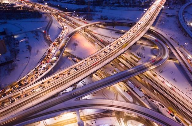 Intercâmbio de transporte complexo de vários níveis, carregado com tráfego, noite de inverno. a estrada é iluminada por lanternas. visão do zangão.