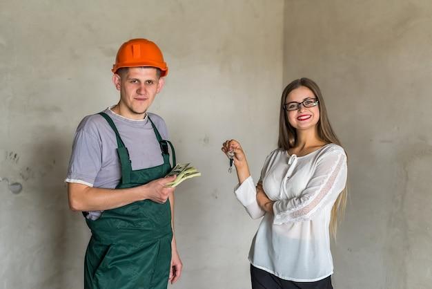 Intercâmbio entre homem construtor com chaves e mulher com dinheiro