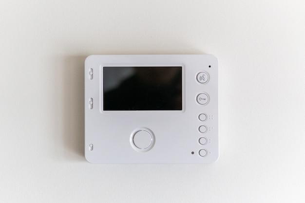 Intercomunicador de vídeo branco em uma parede branca em um apartamento