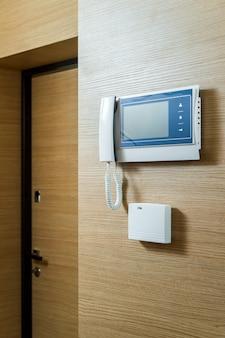 Intercomunicador de vídeo caseiro em uma parede de madeira