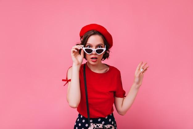 Interessada garota branca com cabelo curto, olhando através de óculos. magnífica mulher francesa em roupa vermelha.