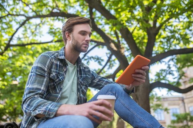 Interessado. um homem com uma camisa xadrez tomando café e assistindo algo em um tablet