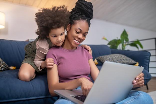 Interessante aqui. mulher afro-americana fofa alegre com corte de cabelo e garotinha encaracolada olhando para o laptop juntos em casa