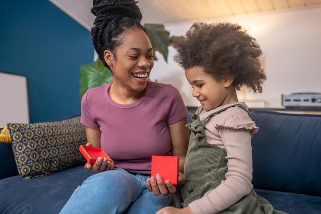 Interessante aqui. mulher alegre de pele escura em camiseta e jeans com uma pequena caixa vermelha aberta e filha sorridente e interessada sentadas juntas no sofá