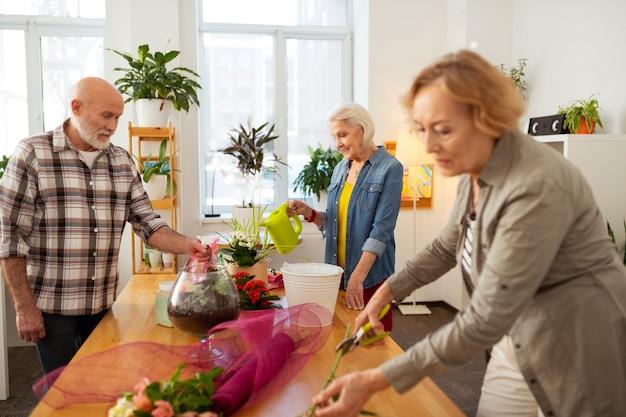 Interesses em comum. idosos agradáveis em pé ao redor de flores enquanto se dedicam à floricultura