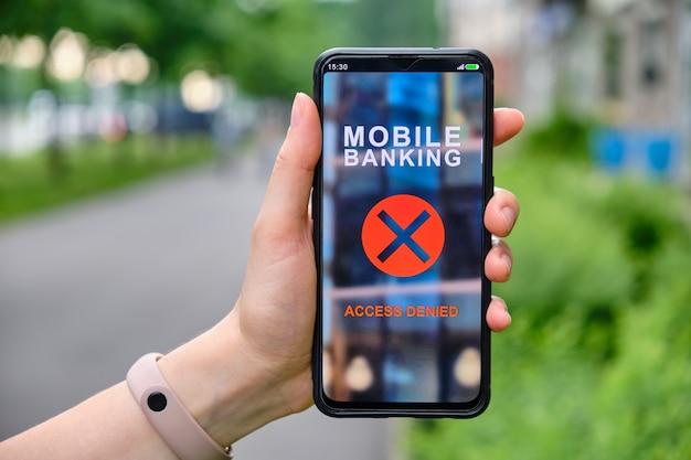 Interface de banco móvel com acesso negado no smartphone e segurando à mão.