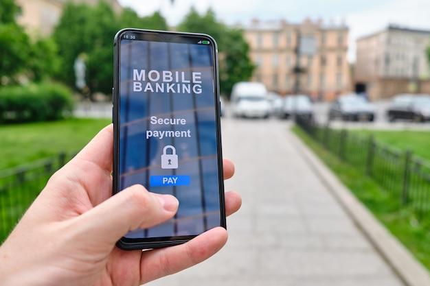 Interface de banco móvel com função de pagamento seguro no smartphone e segurando à mão.