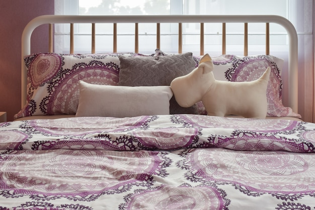 Interior acolhedor quarto com almofadas de padrão roxo na cama