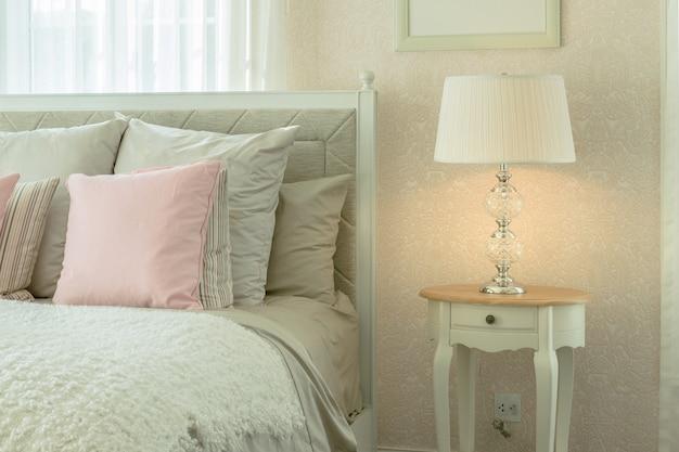 Interior acolhedor quarto com almofadas rosa e lâmpada de leitura na mesa de cabeceira