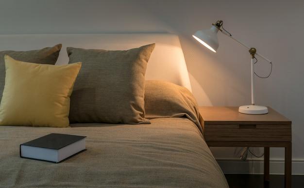 Interior acolhedor quarto com livro e lâmpada de leitura na mesa de cabeceira