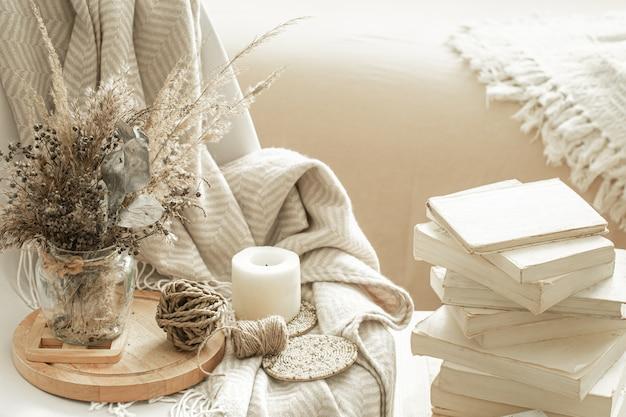 Interior aconchegante da sala com livros e flores secas em um vaso.