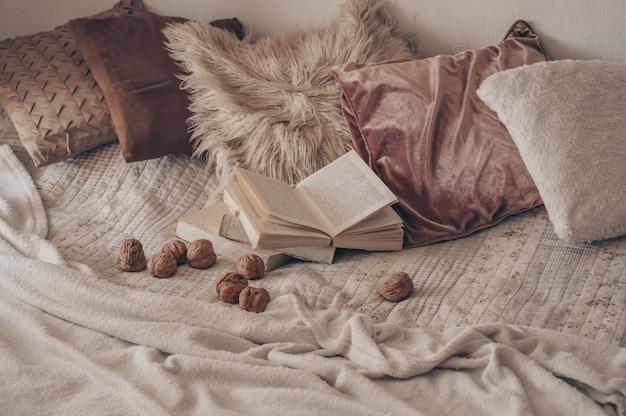 Interior aconchegante da sala de estar com um livro aberto com nozes. leia, descanse. conceito de fim de semana de inverno. conceito aconchegante de outono ou inverno.