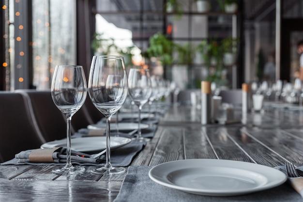 Interior aconchegante do restaurante, serviço de jantar, copos de vinho e água, pratos, garfos e facas, guardanapos de tecido.