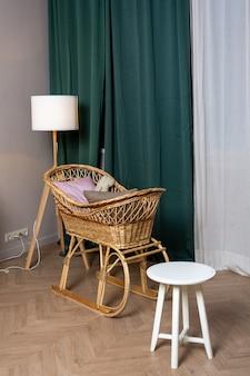 Interior, berço de vime perto da janela com cortinas verdes