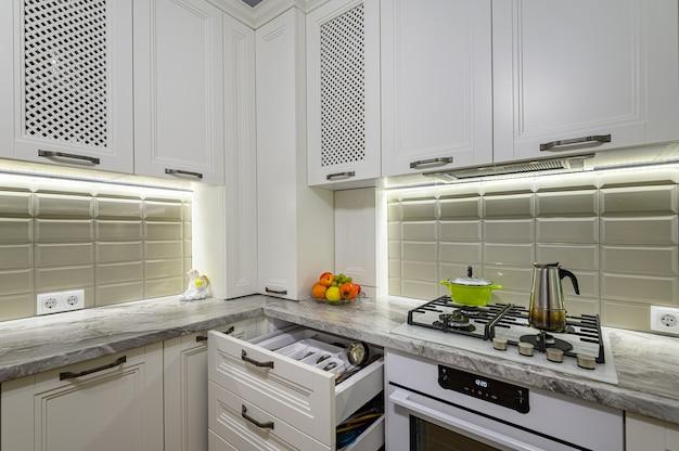 Interior branco, aconchegante e confortável de cozinha clássica contemporânea com móveis de madeira, algumas gavetas são abertas