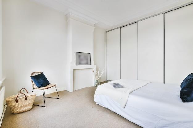 Interior branco claro do quarto com cama grande e mesas de cabeceira perto da janela em arco