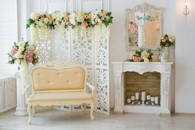 Interior branco clássico da sala de estar com sofá e poltrona perto da lareira.
