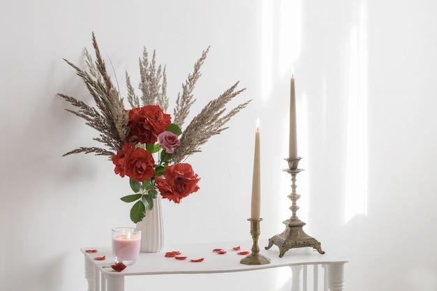 Interior branco com buquê de rosas e velas acesas