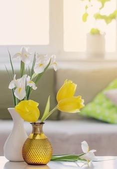 Interior branco da casa com flores e decorações da primavera