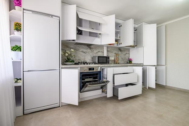 Interior branco da cozinha moderna, algumas gavetas puxadas para fora