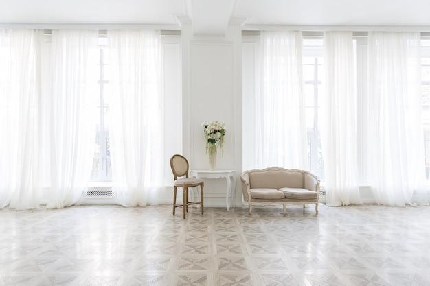 Interior branco luxuoso de sala espaçosa com móveis elegantes e chiques e janelas altas.