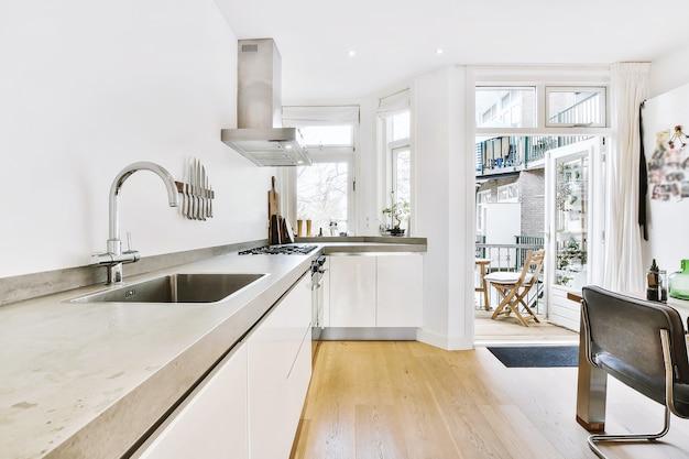 Interior claro da cozinha com balcão cinza e porta aberta que leva à varanda aconchegante do prédio de apartamentos