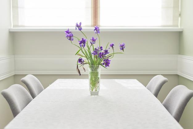 Interior claro da sala de jantar, mesa e cadeiras perto da janela, buquê de íris roxas em um vaso