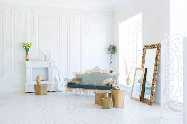Interior claro e luxuoso da sala de estar com parede dourada e móveis elegantes e caros nas cores branco e dourado