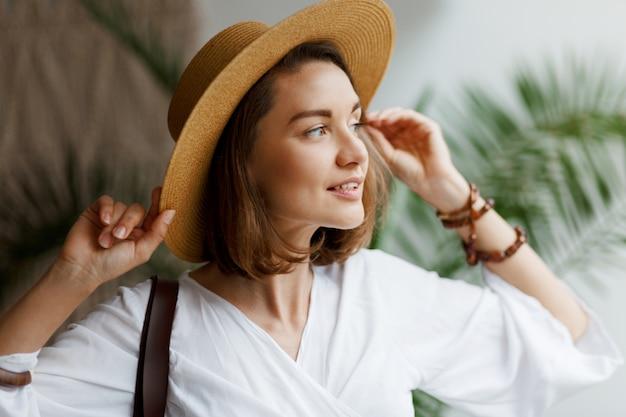Interior close-up retrato de mulher bonita elegante de chapéu de palha e blusa branca posando em casa