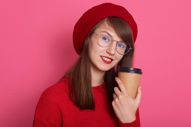 Interior com falta de mulher atraente na boina vermelha, blusa e óculos, segurando a xícara de café ou chá nas mãos isoladas sobre o estúdio-de-rosa